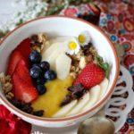 Smoothie bowl con mango, cocco, muesli e frutti rossi